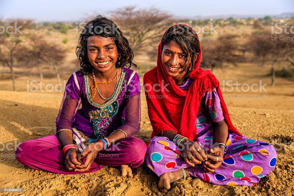 Happy Indian girls sitting on sand dune, desert village, India stock photo