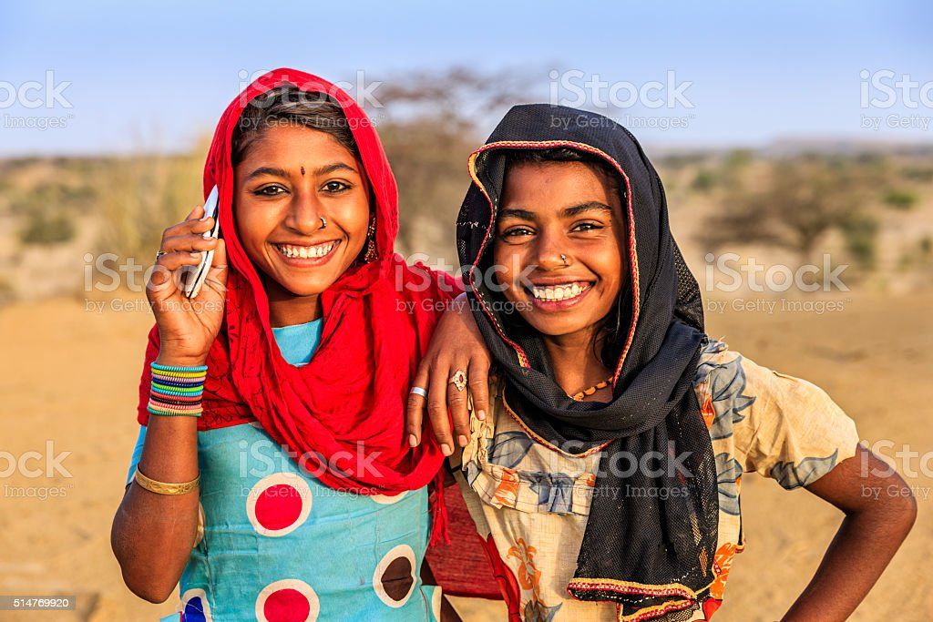 Happy Indian girls using mobile phone in desert village, India stock photo