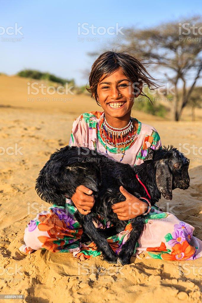 Happy Indian little girl holding a goat, desert village, India stock photo