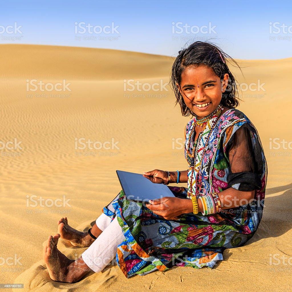 Happy Indian little girl using digital tablet, desert village, India stock photo