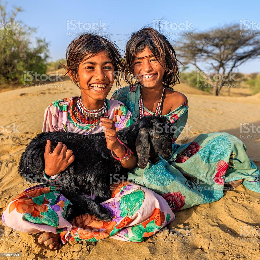 Happy Indian little girls holding a goat, desert village, India stock photo