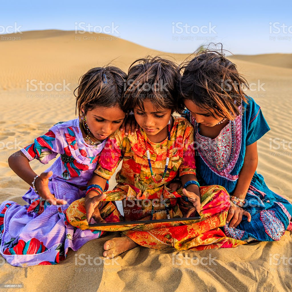 Happy Indian little girls using digital tablet, desert village, India stock photo