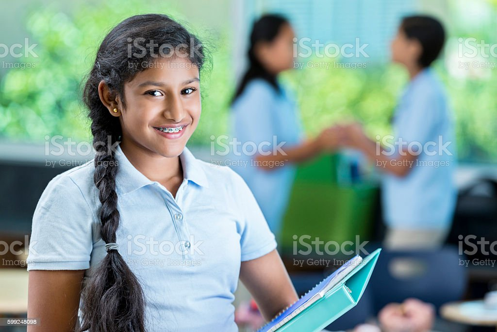 Happy Indian middle school student smiles before class stock photo