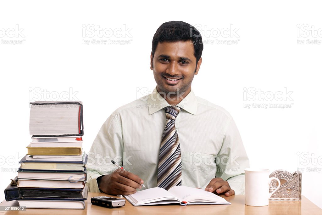 Happy Indian young businessman writing stock photo