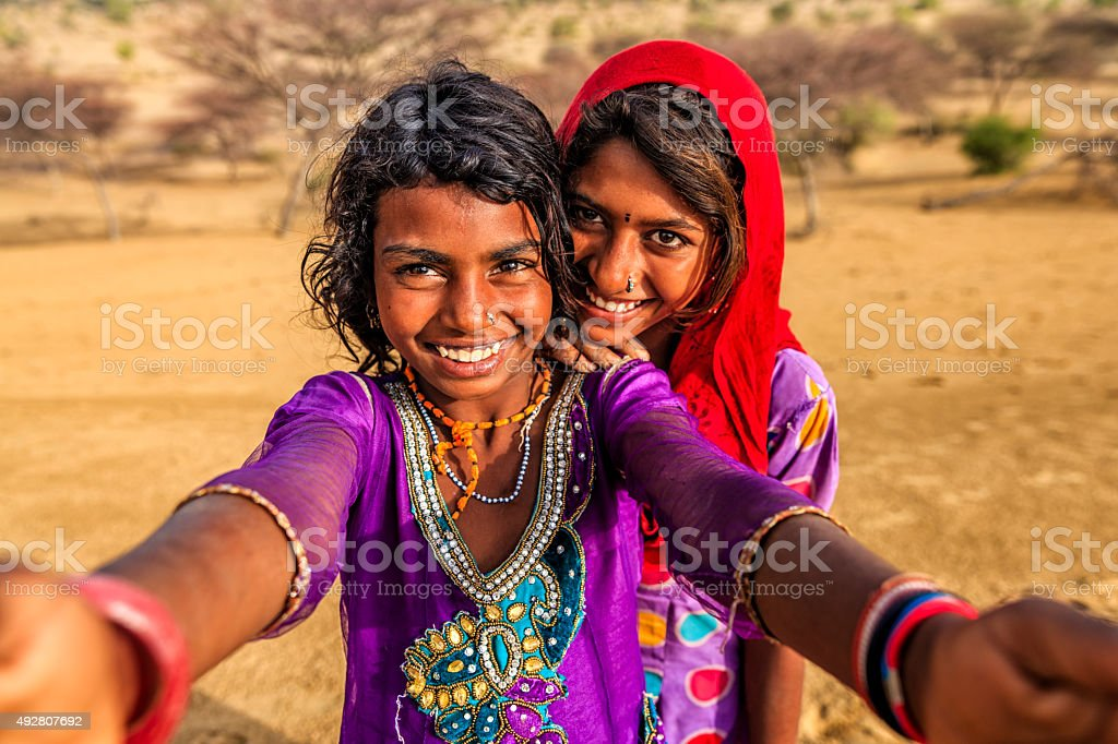 Happy Indian young girls taking selfie, desert village, India stock photo