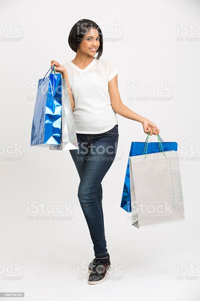 Happy Indian young woman posing with shopping bags stock photo