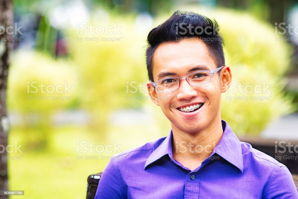 Happy Indonesian male student portrait with braces and glasses stock photo