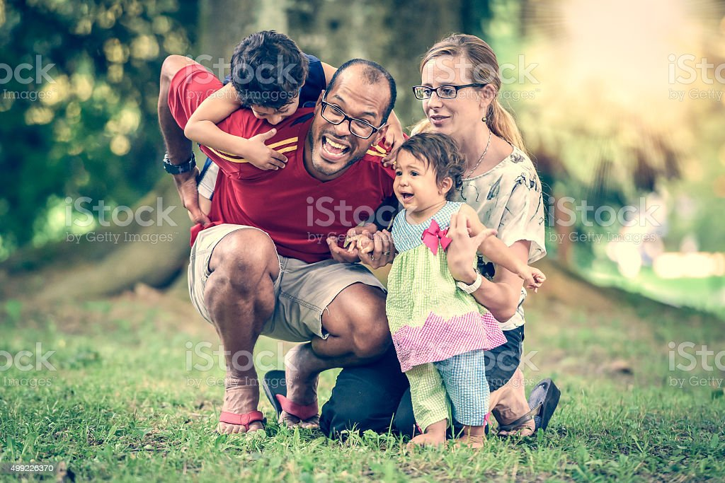 Happy interracial family is being active a day the park stock photo