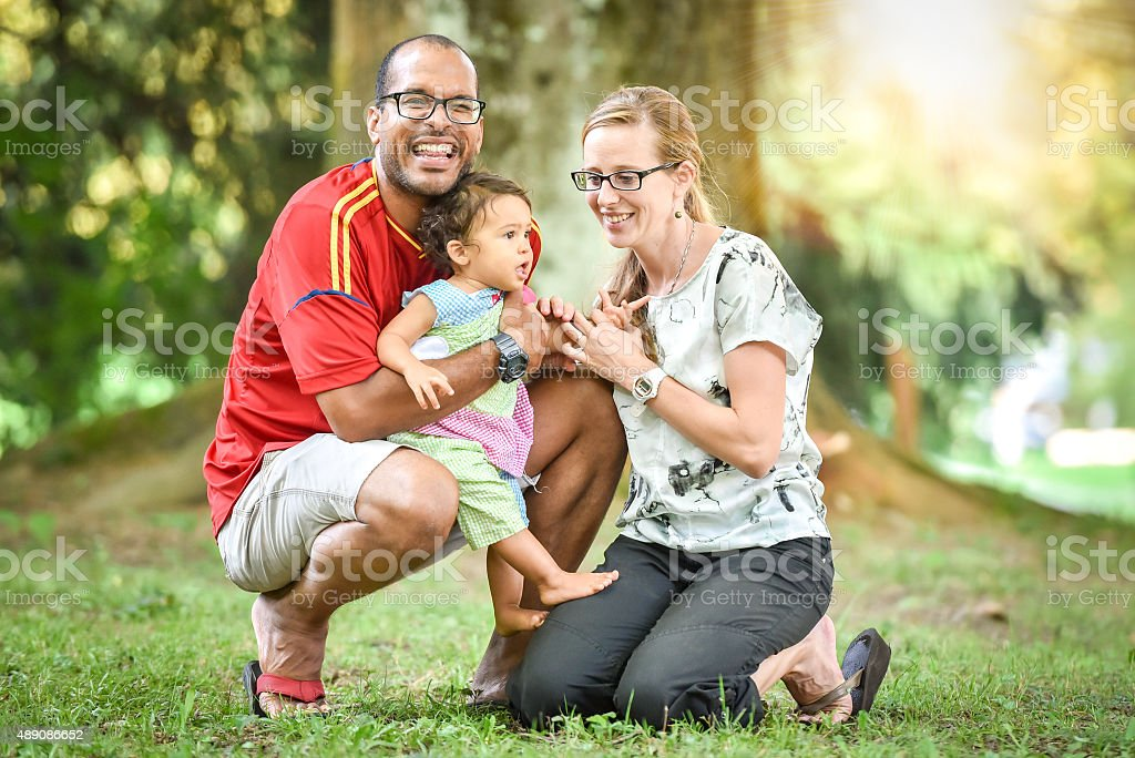 Happy interracial family is enjoying a day in the park stock photo