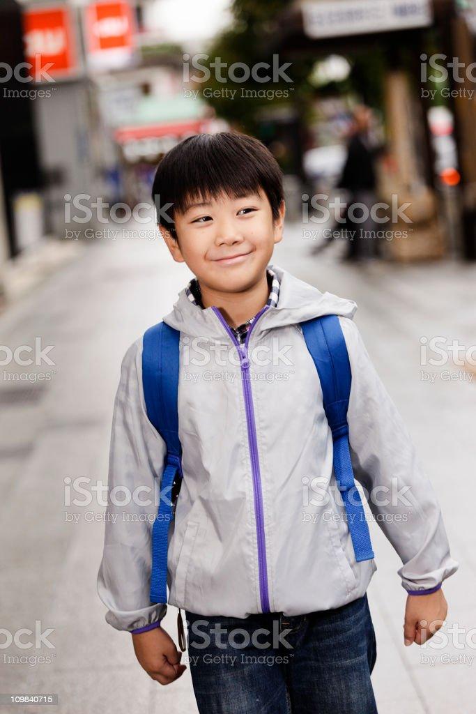 Happy Japanese Boy Walking on a Sidewalk royalty-free stock photo