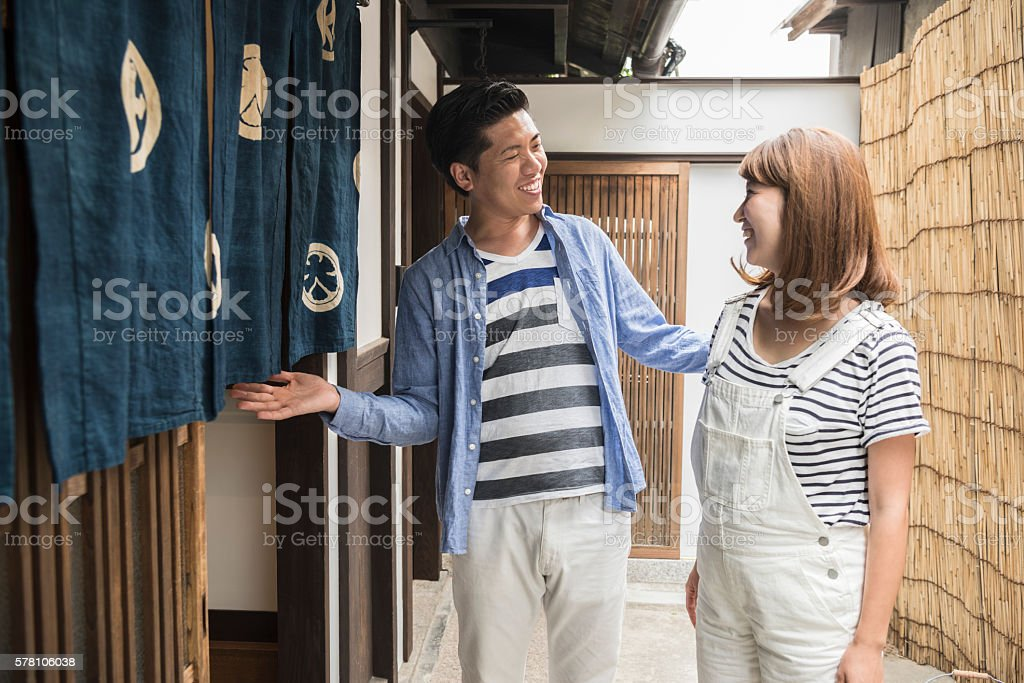 Happy Japanese couple outside front door of traditional home stock photo