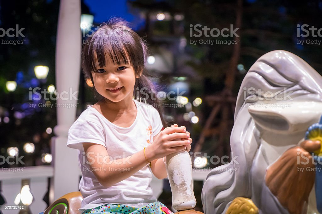 Happy Japanese girl on a horse carousel with bokeh background stock photo