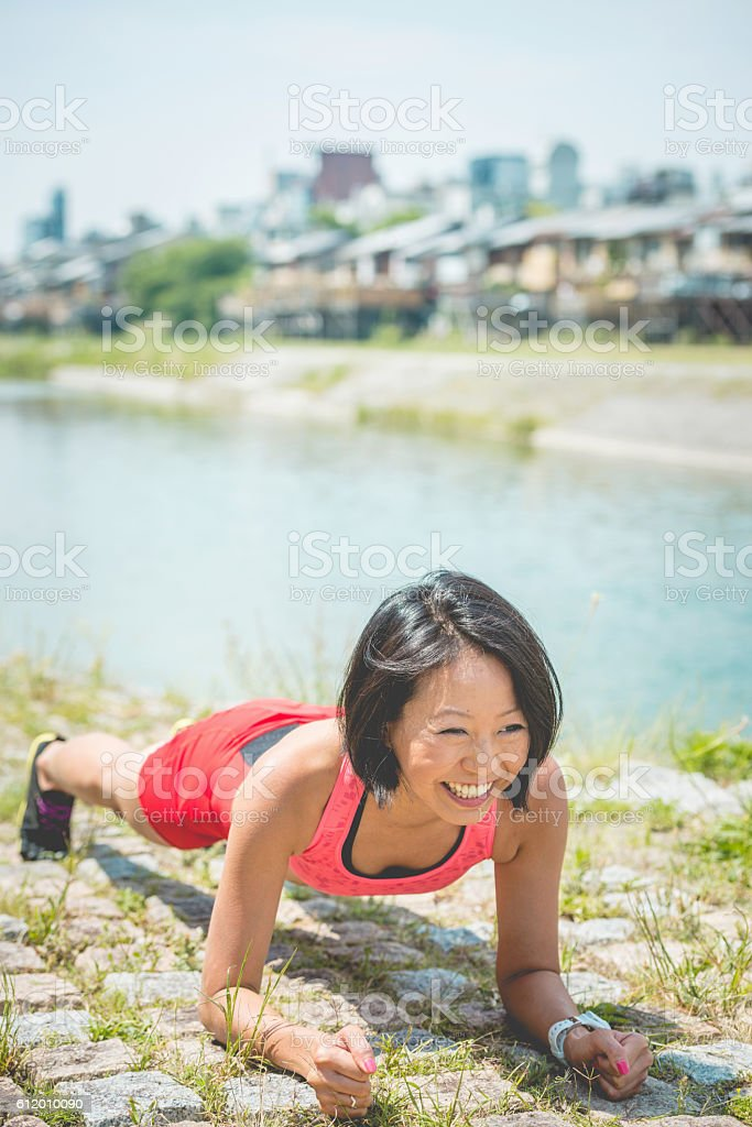Happy Japanese Jogger Doing Yoga, Kamo River, Kyoto, Japan stock photo