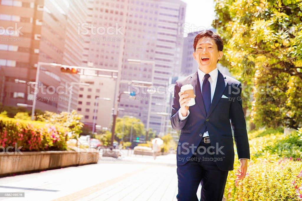 Happy Japanese office worker urban portrait walking down Tokyo street stock photo