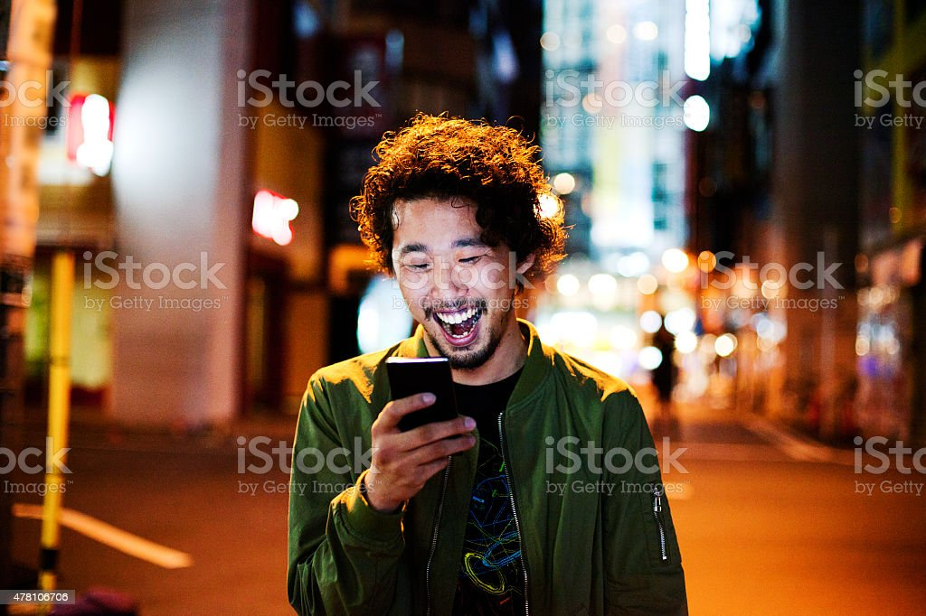 Happy japanese young man with smart phone at night, Tokyo. stock photo