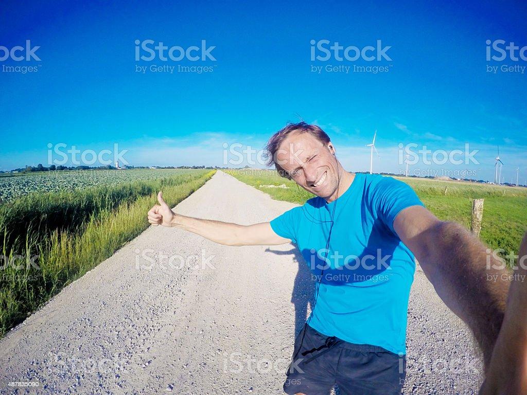 Happy jogger on dust road, GoPro image stock photo