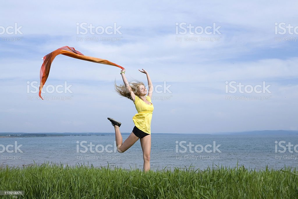 Happy jumping girl at the water view with a streamer. royalty-free stock photo