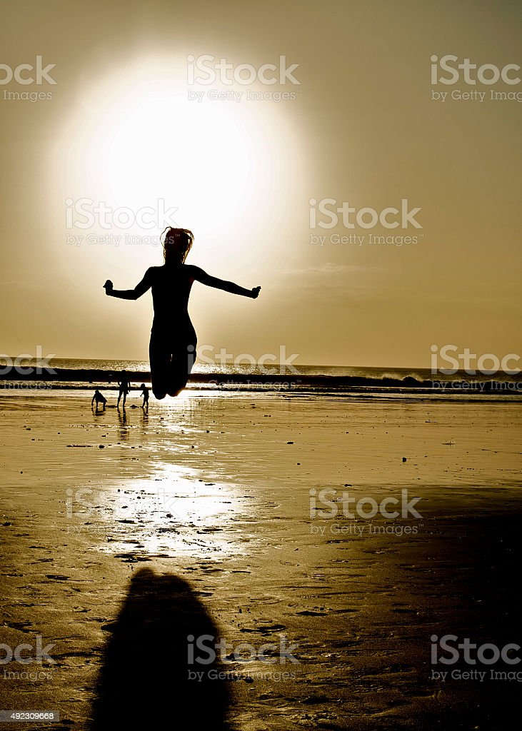 Happy jumping girl on beach. Holidays by sea. Sunny day. stock photo