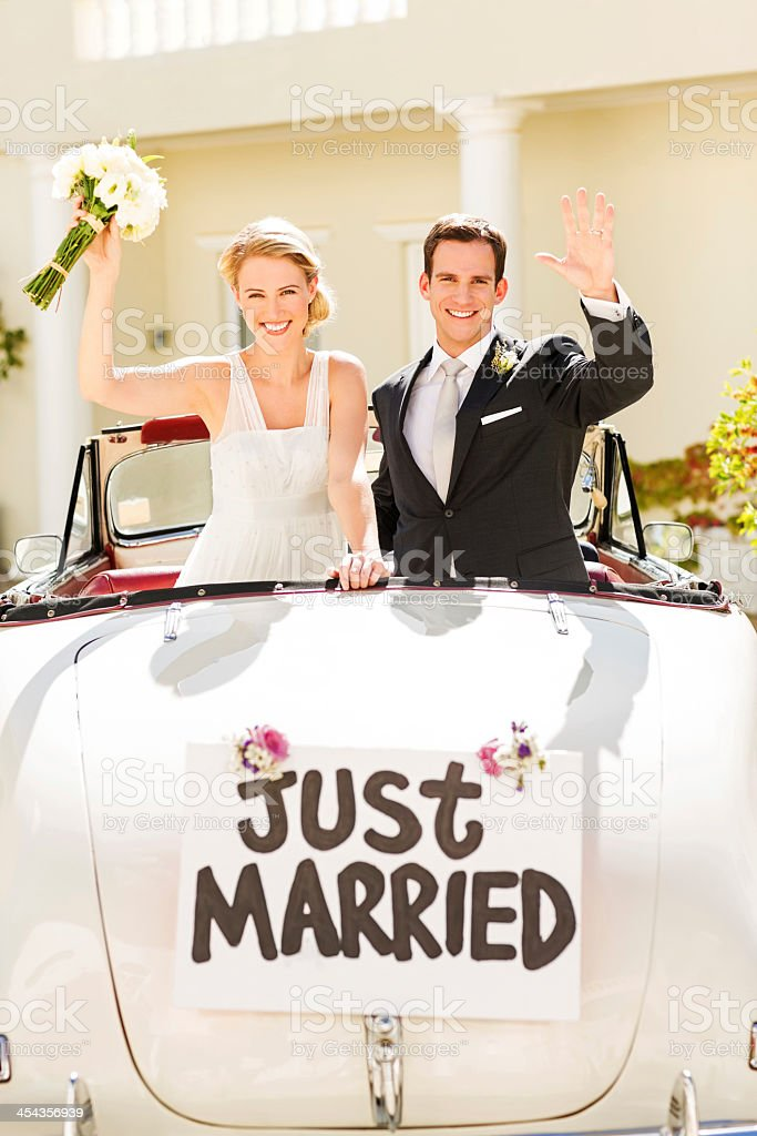 Happy Just Married Couple Waving In Car stock photo