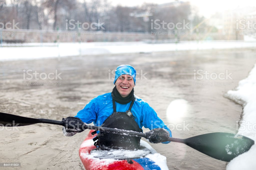 Happy Kayaker driving kayak on winter and laughing stock photo