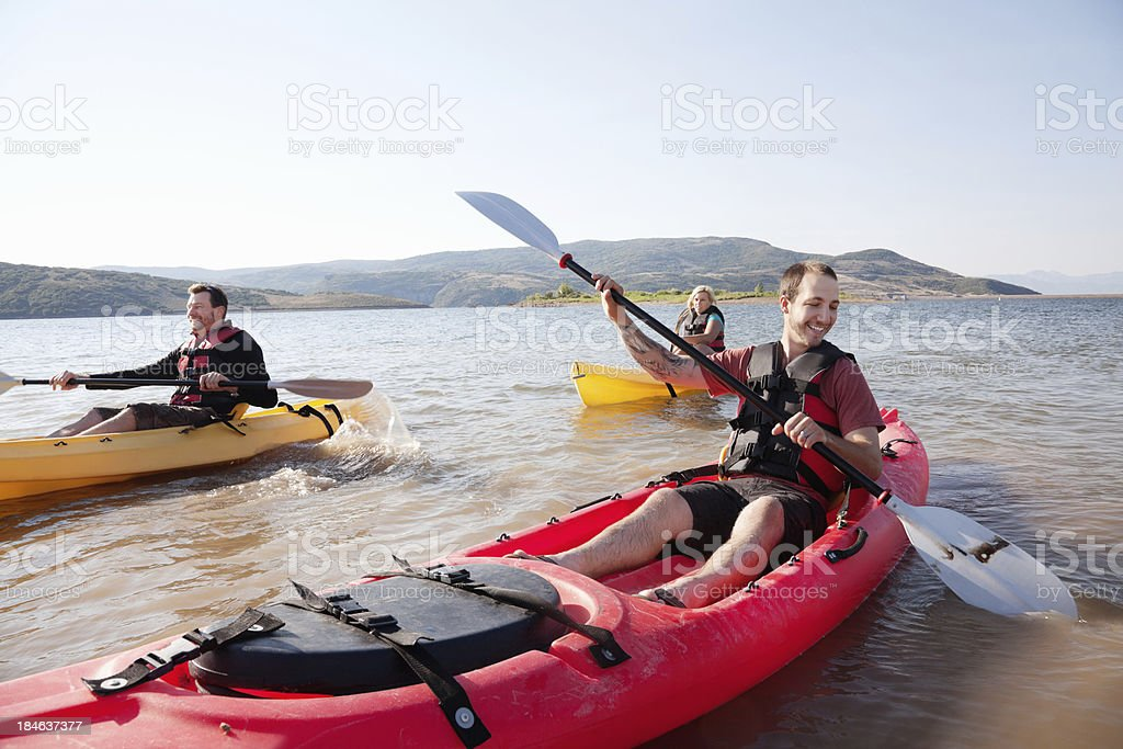 Happy kayakers rowing on a lake royalty-free stock photo
