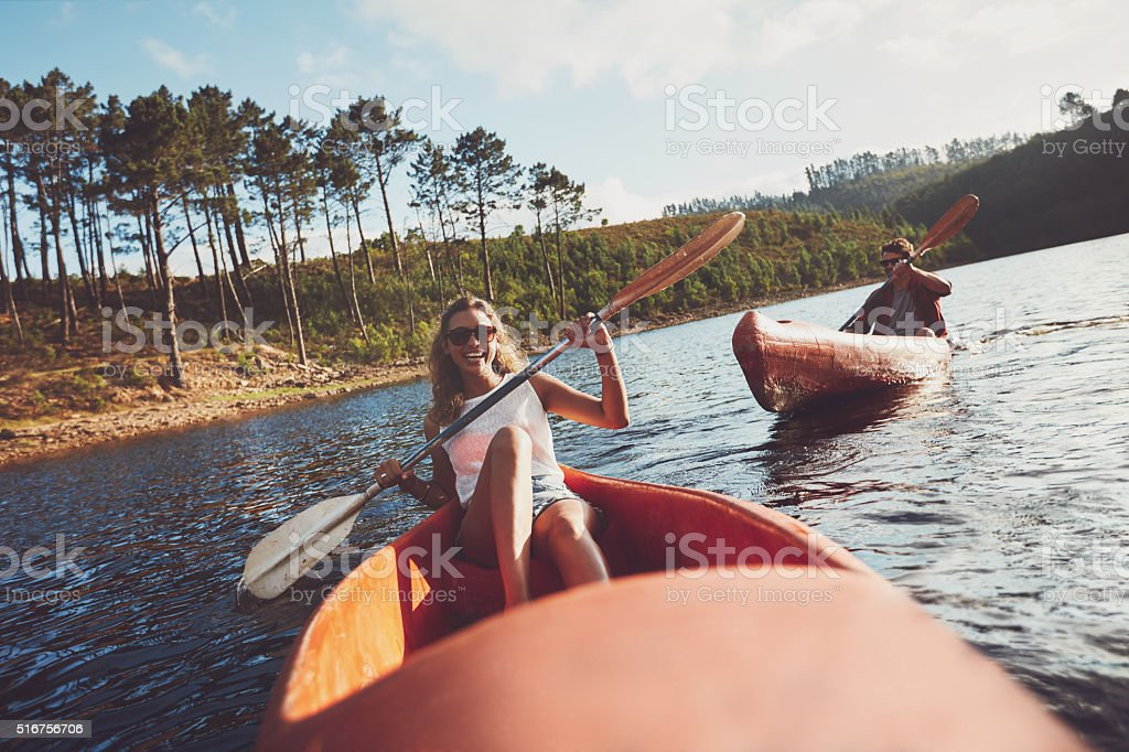 Happy kayakers rowing on a lake stock photo