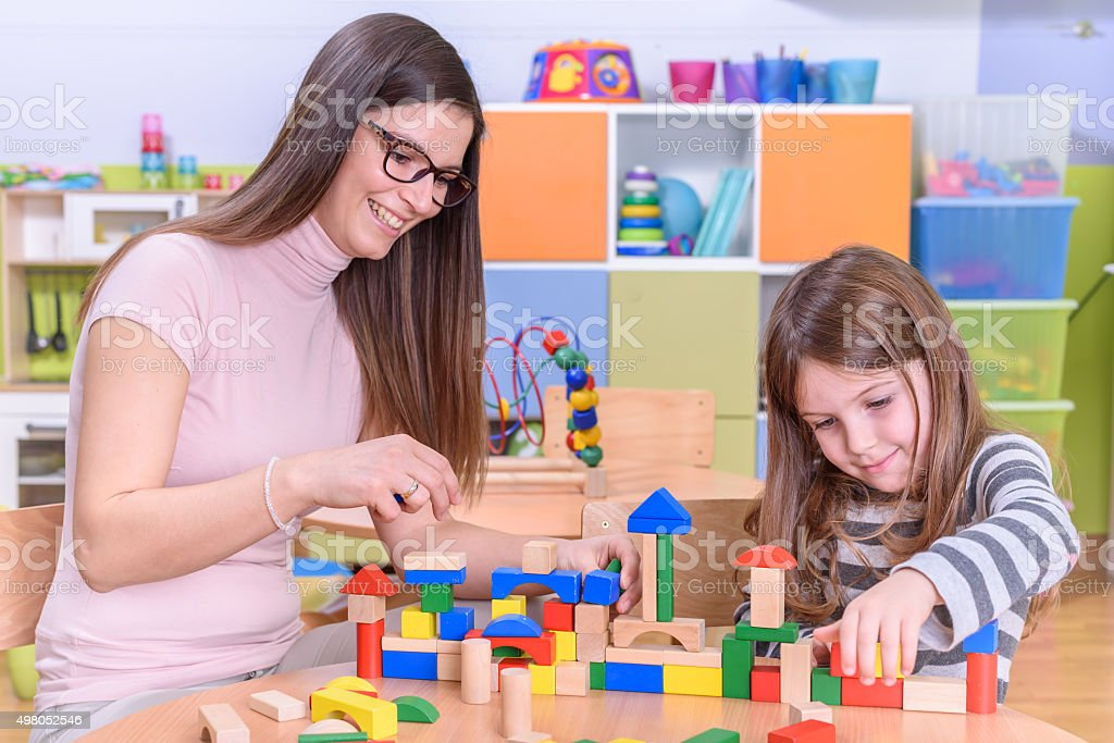 Happy Kid and Kindergarten Teacher Playing with Building Blocks stock photo