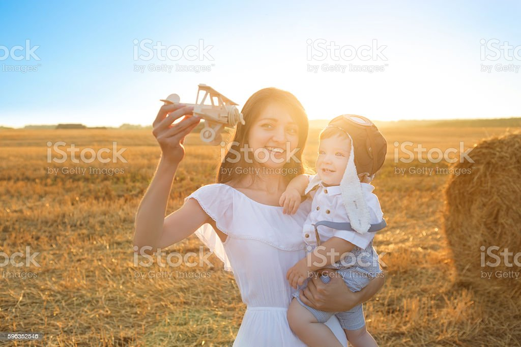 Happy kid and woman playing with toy airplane against field. stock photo
