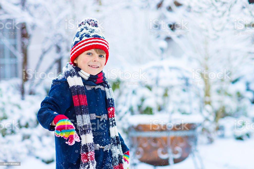 Happy kid boy having fun with snow in winter stock photo
