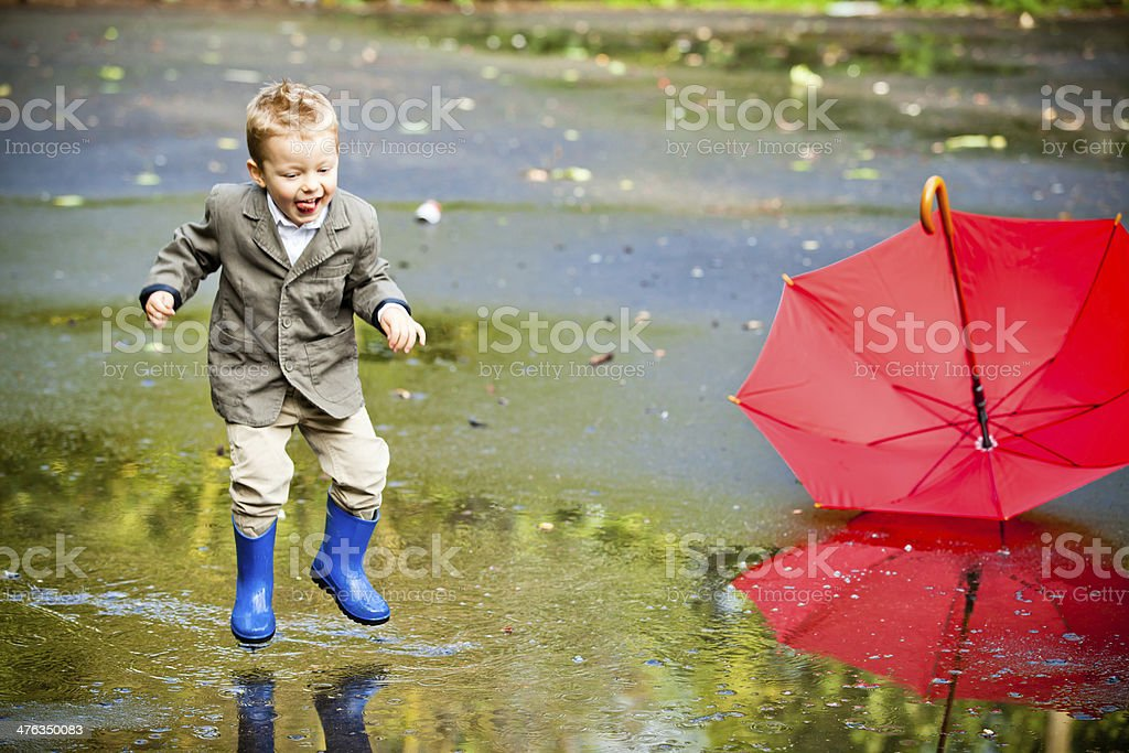 Happy kid in wellingtons stock photo