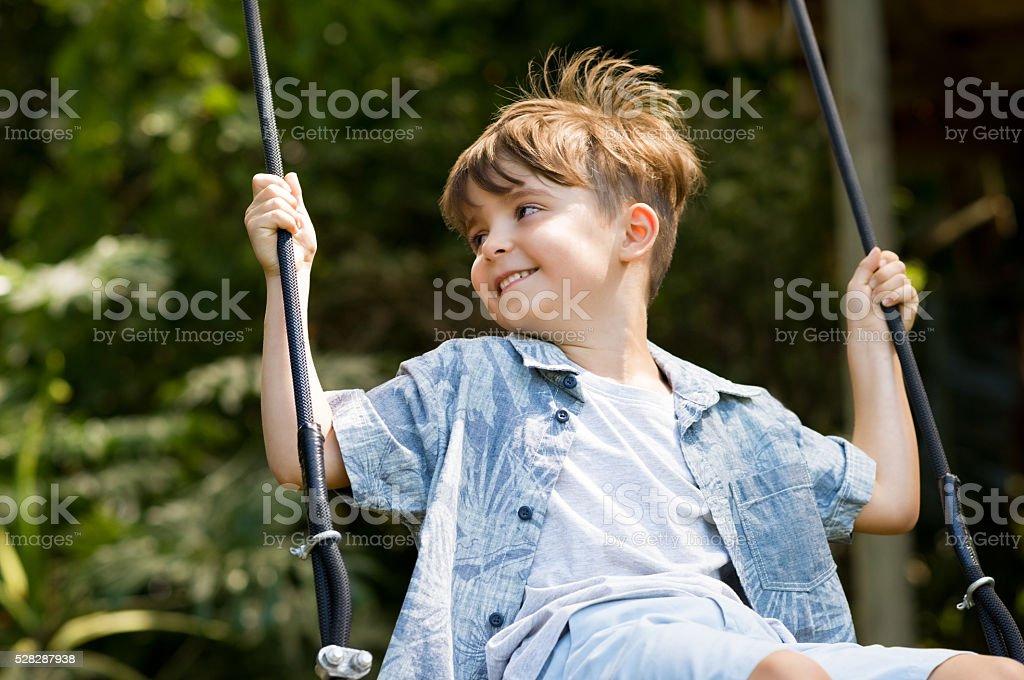 Happy kid on swing stock photo