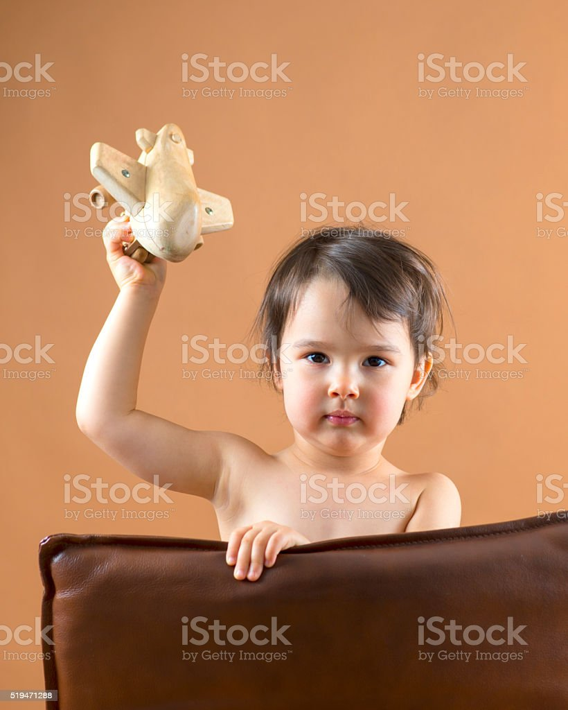 Happy kid playing with toy airplane. Studio shot. stock photo