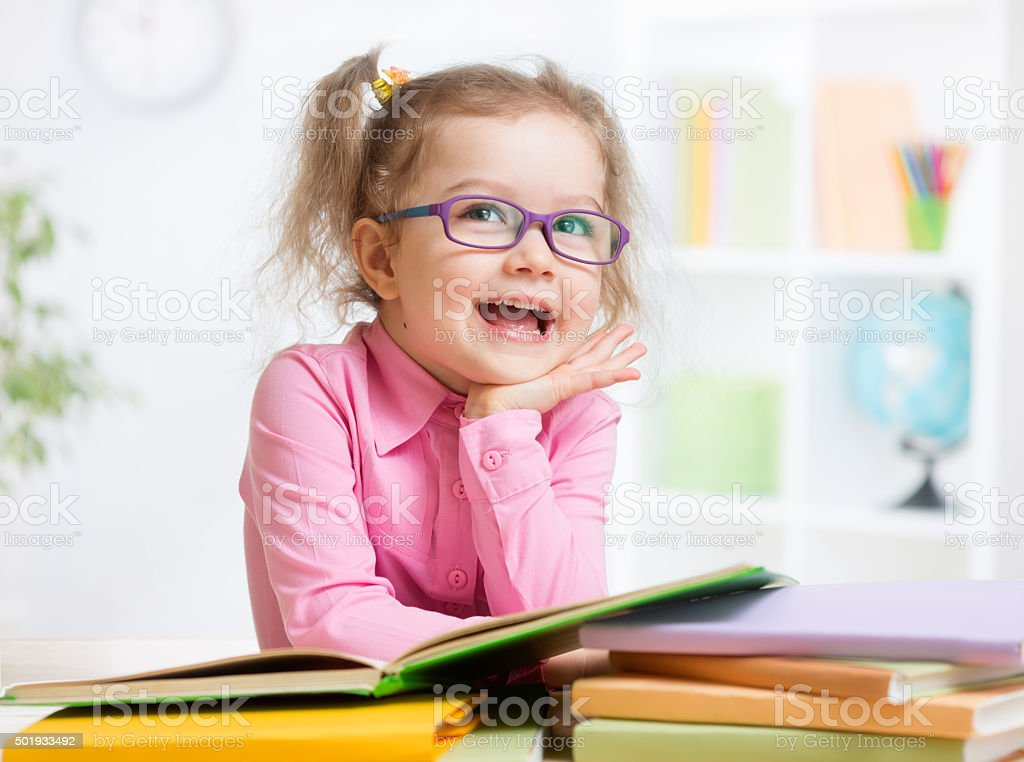 Happy kid reading books and dreaming stock photo