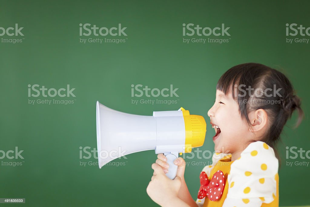 happy kid shouts something into the megaphone stock photo