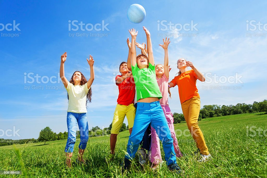 Happy kids catching ball in air outside stock photo