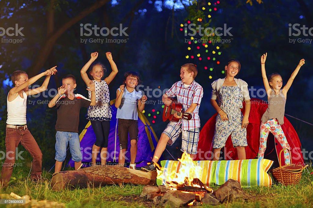 happy kids dancing around campfire stock photo