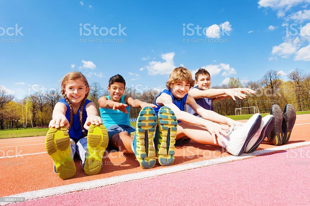 Happy kids doing stretching exercises on a stadium stock photo