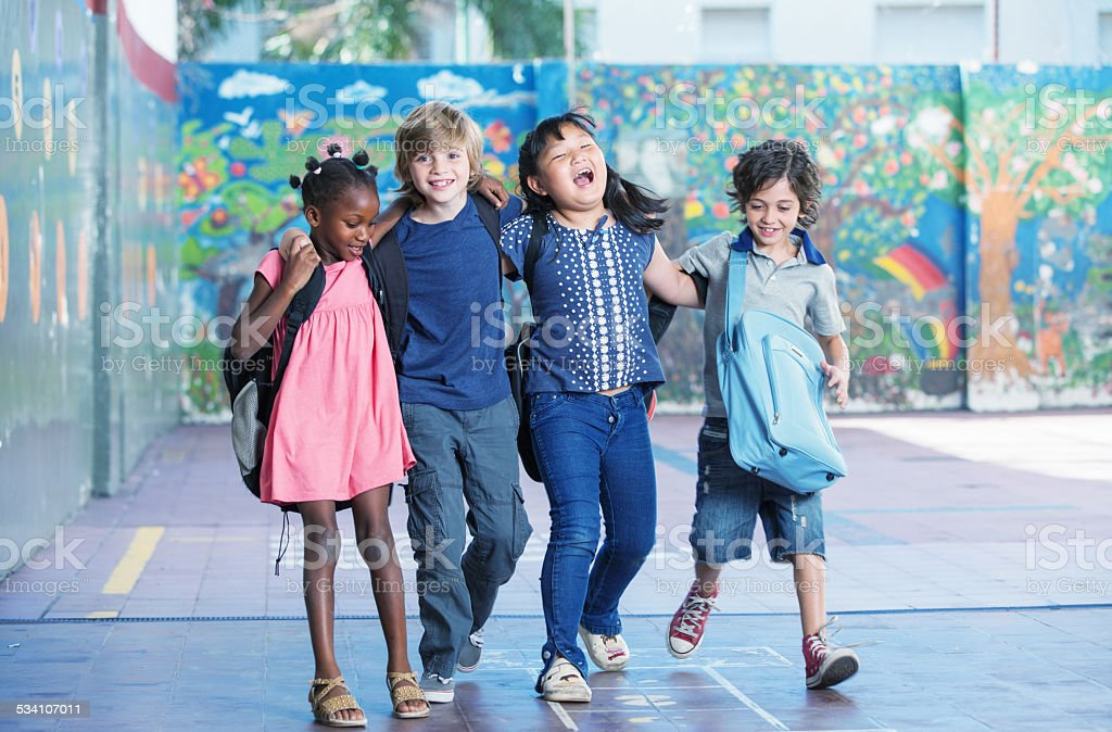 Happy kids embracing and smiling in the elementary schoolyard. I stock photo