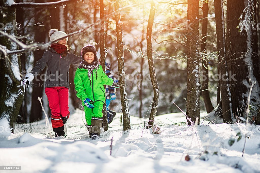 Happy kids enjoying sunny winter day in forest stock photo