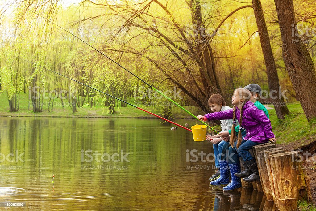 Happy kids fishing together near beautiful pond stock photo