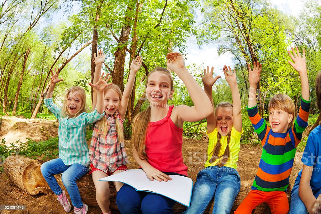 Happy kids having fun reading a book in the forest stock photo