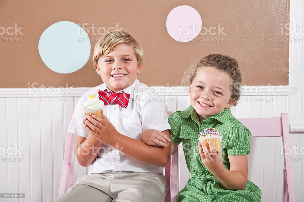 Happy kids holding cupcakes stock photo