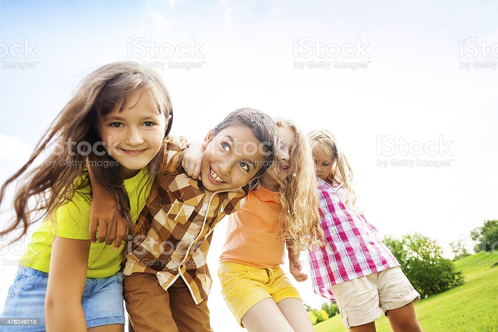 Happy kids hugging toggether stock photo