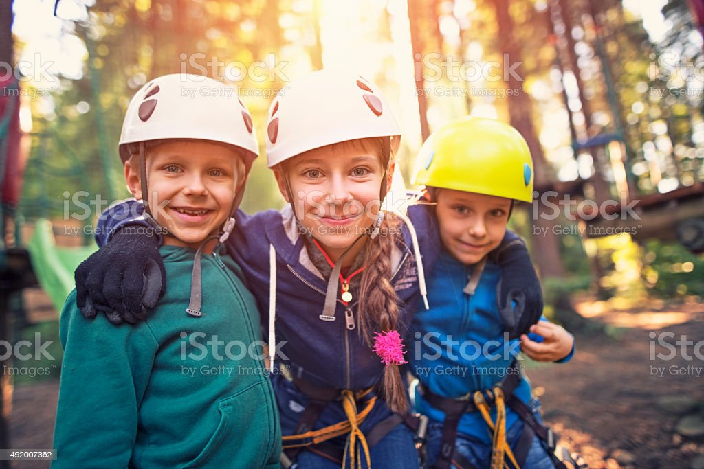 Happy kids in ropes course adventure park stock photo