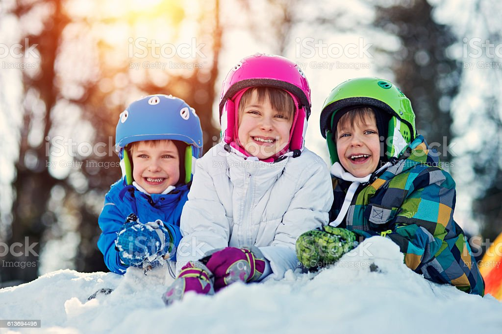 Happy kids in ski outfits enjoying winter stock photo