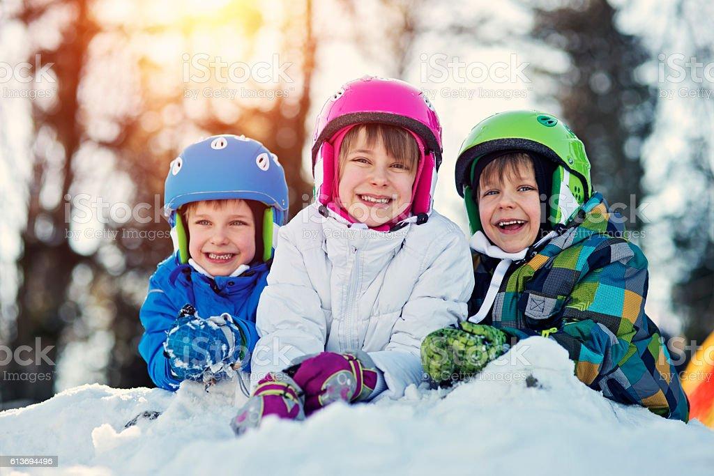 Happy kids in ski outfits enjoying winter stock photo