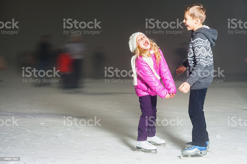 Happy kids laughing at ice rink outdoor, ice skating stock photo
