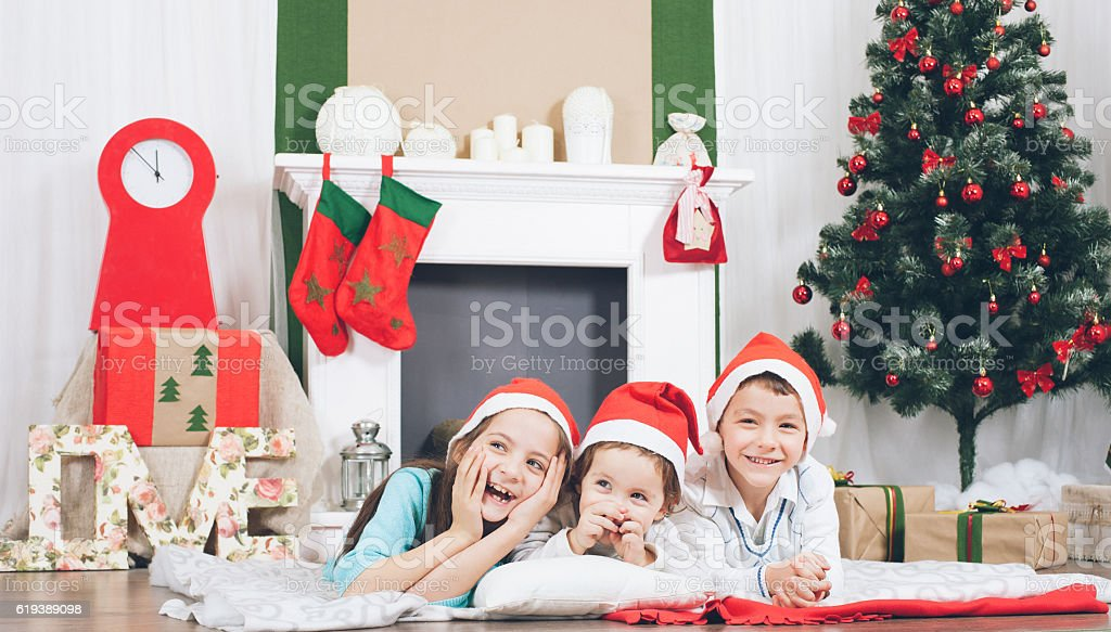 happy kids laughing  on  background of christmas tree and fireplace stock photo