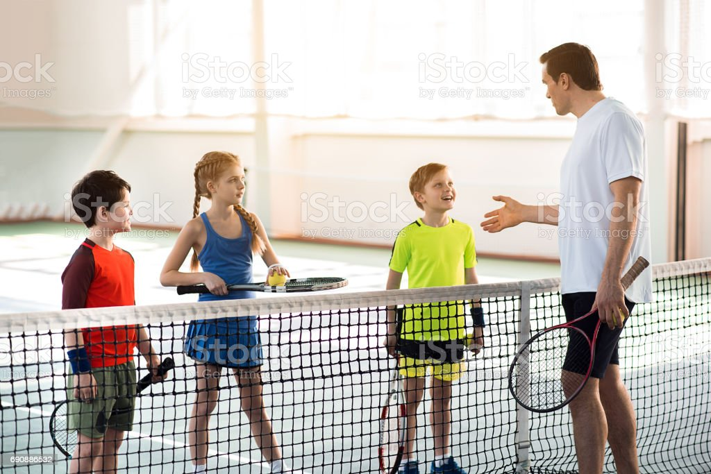 Confident male trainer is explaining how to play tennis to children....