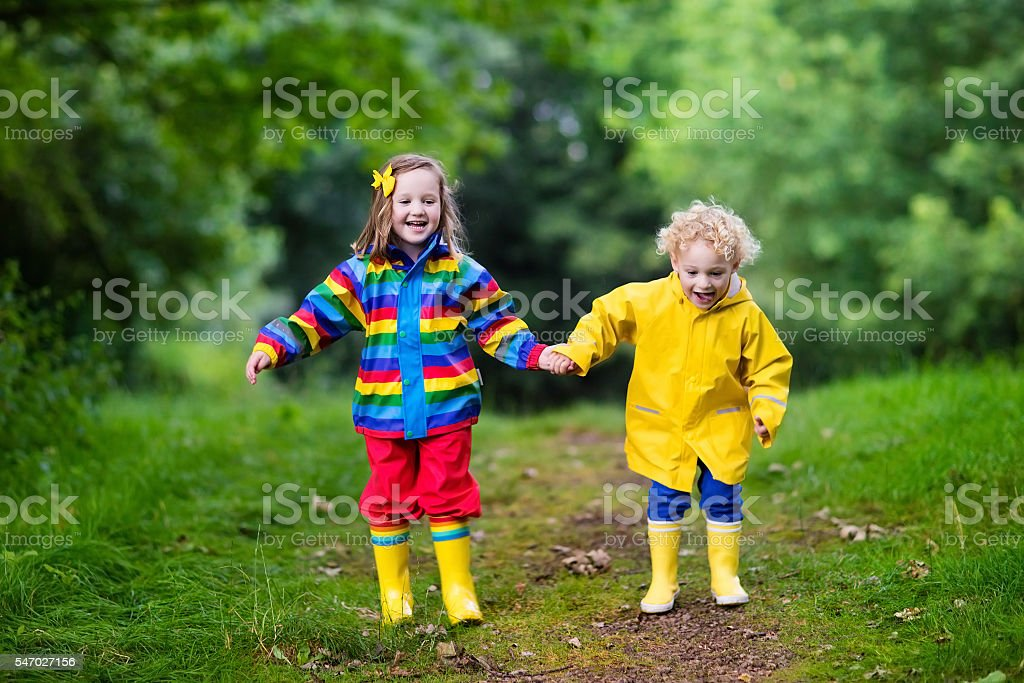 Happy kids playing in mud in the rain stock photo